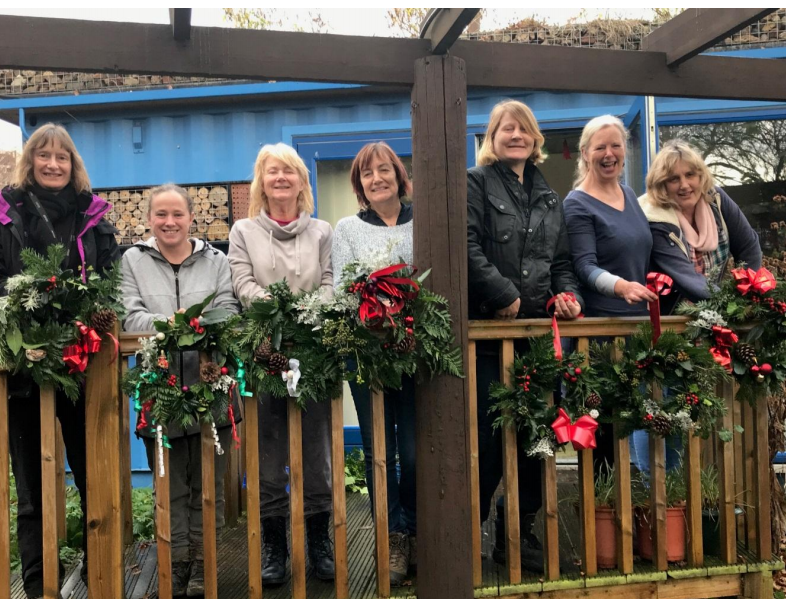 Members with Victorian-style Christmas wreaths